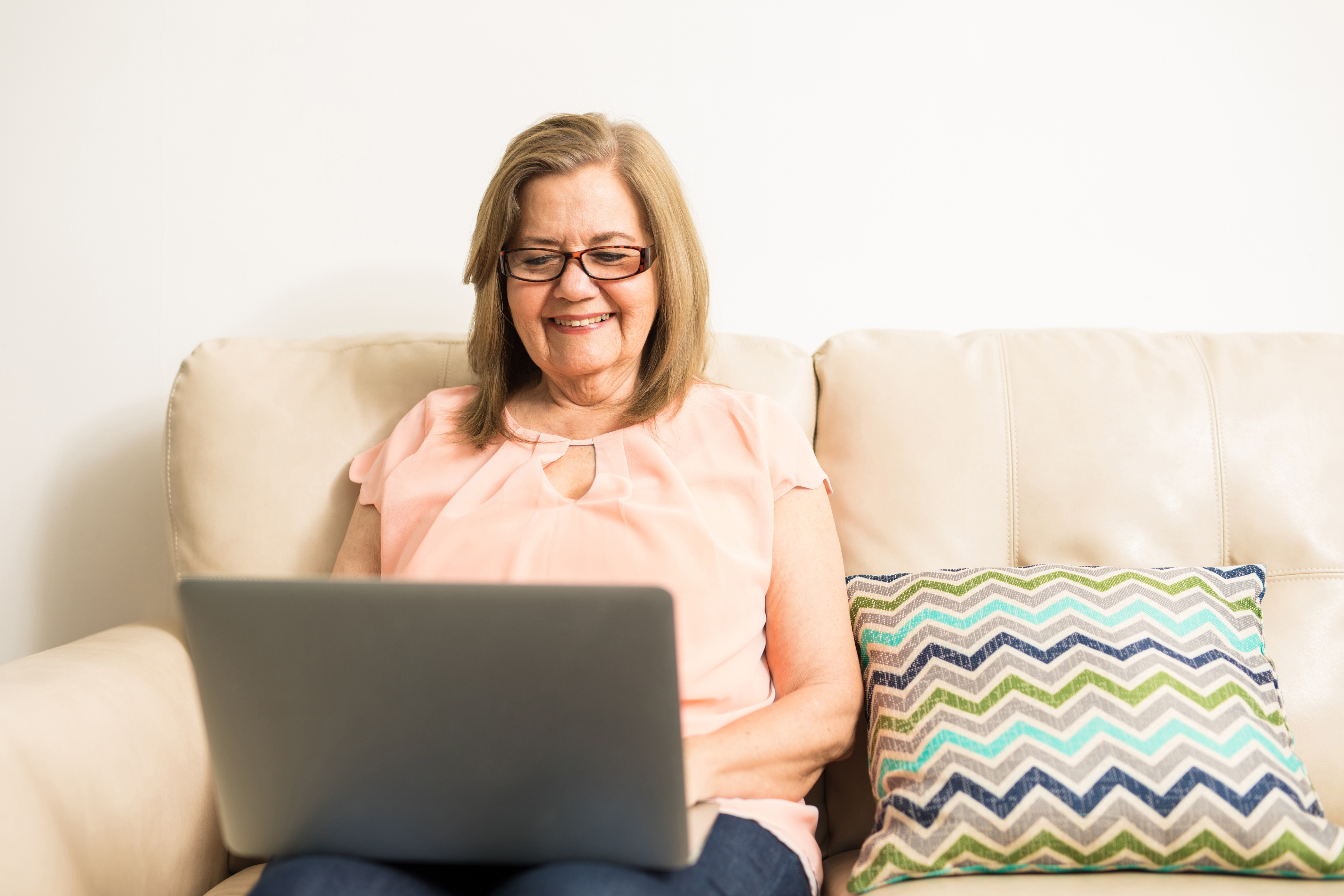Active beautiful woman using her glasses to read from her computer on his legs in the living room